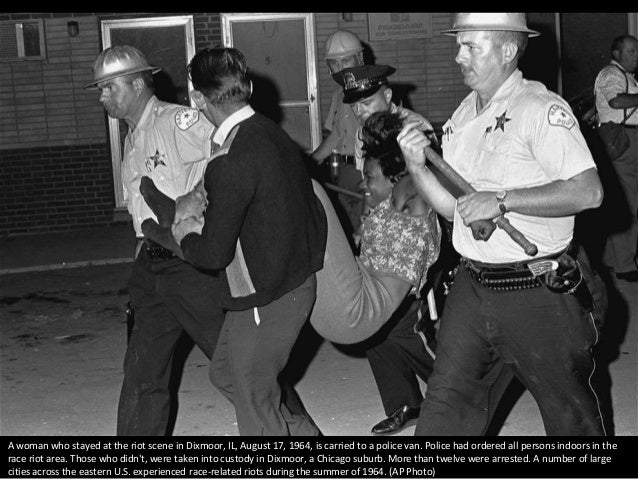 A woman who stayed at the riot scene in Dixmoor, IL, August 17, 1964, is carried to a police van. Police had ordered all p...
