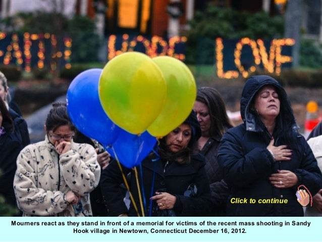 Click to continueMourners react as they stand in front of a memorial for victims of the recent mass shooting in Sandy     ...