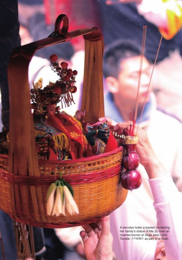 A devotee holds a basket containing                       her family's statue of Ma Zu over an                       incen...