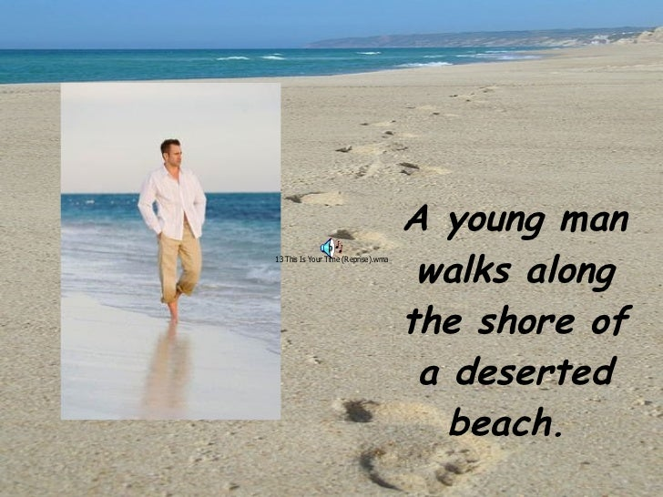 A young man walks along the shore of a deserted beach.
