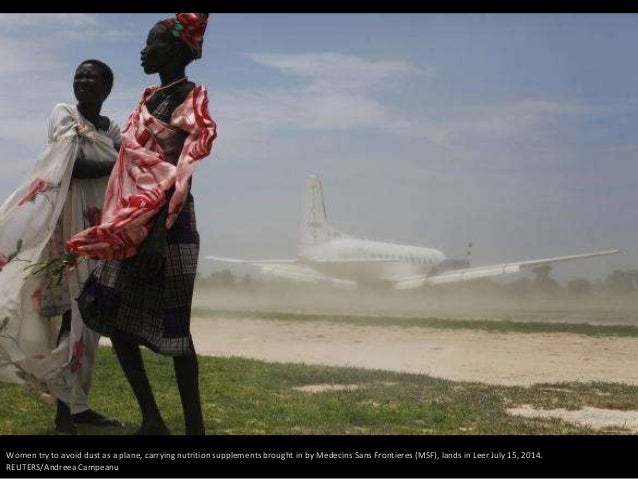 Women try to avoid dust as a plane, carrying nutrition supplements brought in by Medecins Sans Frontieres (MSF), lands in ...