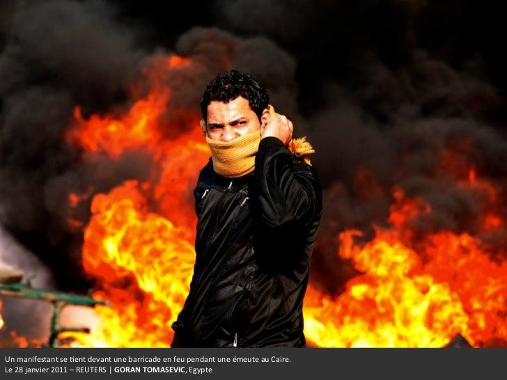 Un manifestant se +ent devant une barricade en feu pendant une émeute au Caire.  Le 28 j...