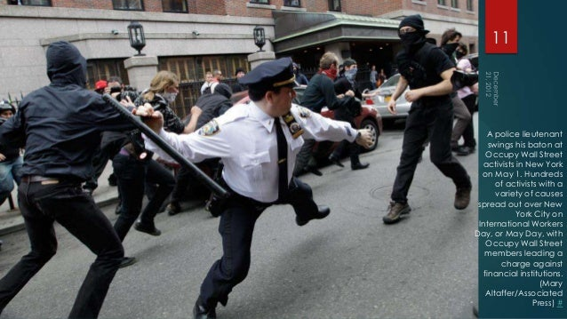 11    A police lieutenant     swings his baton at    Occupy Wall Street  activists in New York  on May 1. Hundreds       o...