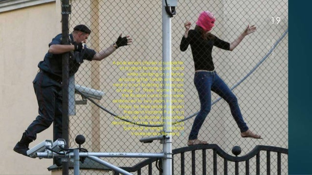 19A policeman chases a supporter   of a jailed female punk band        while climbing on a fence   enclosing the Turkish e...
