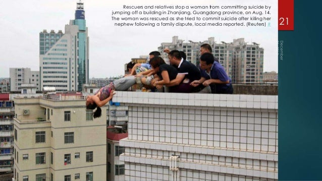 Rescuers and relatives stop a woman from committing suicide byjumping off a building in Zhanjiang, Guangdong province, on ...
