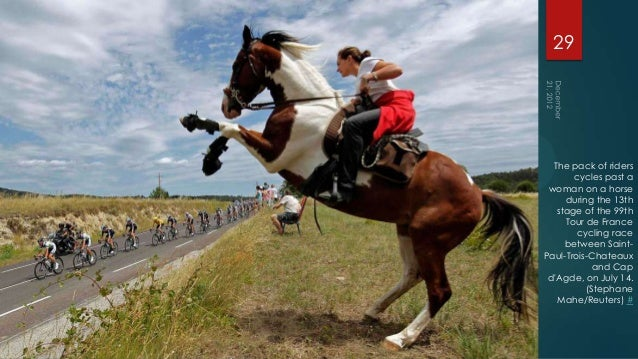 29  The pack of riders       cycles past a woman on a horse     during the 13th   stage of the 99th     Tour de France    ...