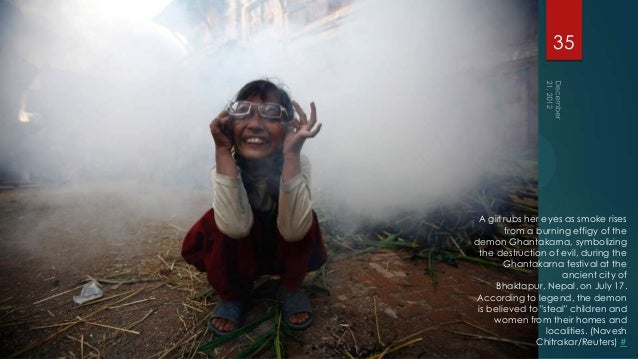 35 A girl rubs her eyes as smoke rises        from a burning effigy of thedemon Ghantakarna, symbolizing the destruction o...