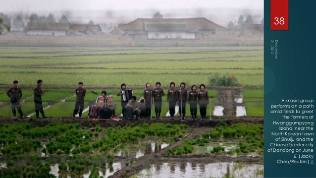 38        A music group performs on a path amid fields to greet        the farmers at   Hwanggumpyong      Island, near th...