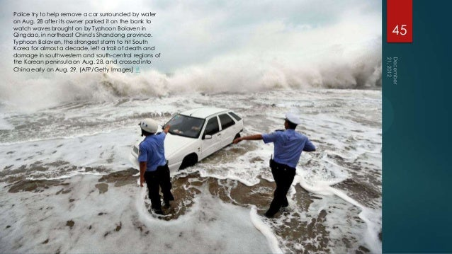 Police try to help remove a car surrounded by wateron Aug. 28 after its owner parked it on the bank towatch waves brought ...