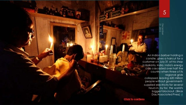 5     An Indian barber holding a    candle, gives a haircut for acustomer on July 31 at his shopin Kolkata, India. Indias ...
