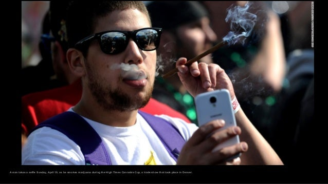 A man takes a selfie Sunday, April 19, as he smokes marijuana during the High Times Cannabis Cup, a trade show that took p...