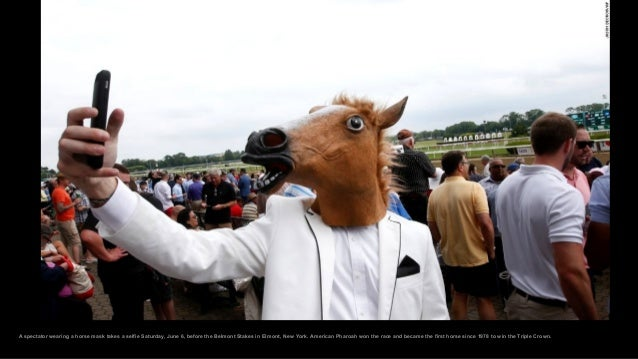 A spectator wearing a horse mask takes a selfie Saturday, June 6, before the Belmont Stakes in Elmont, New York. American ...