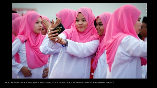 Members of Malaysia's largest political party, the United Malays National Organization, take a selfie at the party's gener...