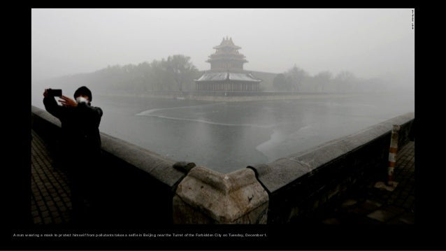 A man wearing a mask to protect himself from pollutants takes a selfie in Beijing near the Turret of the Forbidden City on...