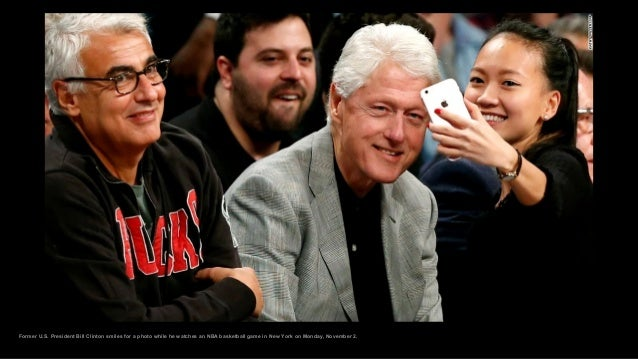Former U.S. President Bill Clinton smiles for a photo while he watches an NBA basketball game in New York on Monday, Novem...