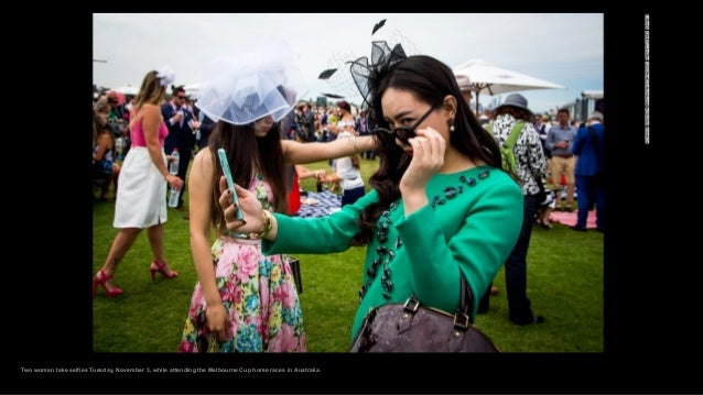 Two women take selfies Tuesday, November 3, while attending the Melbourne Cup horse races in Australia.