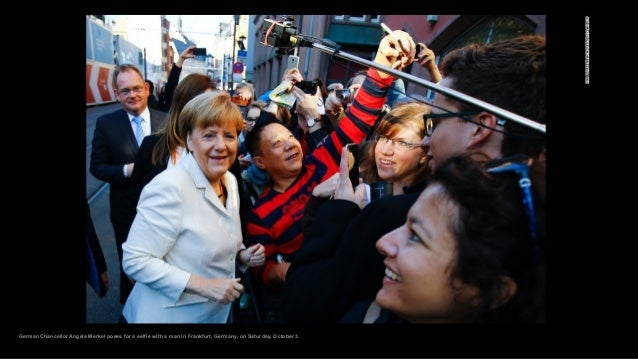 German Chancellor Angela Merkel poses for a selfie with a man in Frankfurt, Germany, on Saturday, October 3.