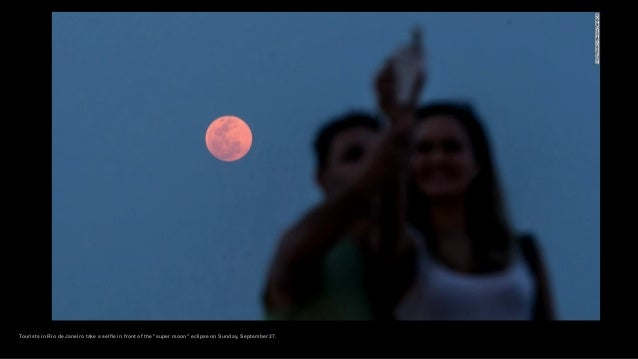 """Tourists in Rio de Janeiro take a selfie in front of the """"super moon"""" eclipse on Sunday, September 27."""