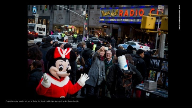 Pedestrians take a selfie in front of Radio City Music Hall in New York on Sunday, December 20.