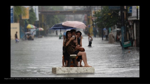 People in Manila, Philippines, take a selfie Wednesday, August 12, as they ride on a makeshift raft in a flooded street.