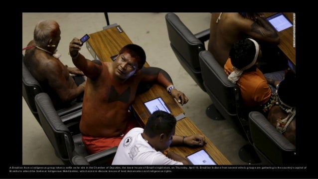 A Brazilian from a indigenous group takes a selfie as he sits in the Chamber of Deputies, the lower house of Brazil's legi...