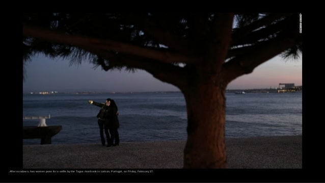 After sundown, two women pose for a selfie by the Tagus riverbank in Lisbon, Portugal, on Friday, February 27.