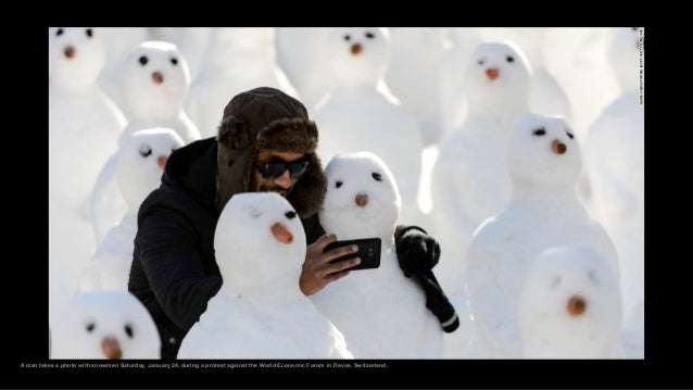A man takes a photo with snowmen Saturday, January 24, during a protest against the World Economic Forum in Davos, Switzer...