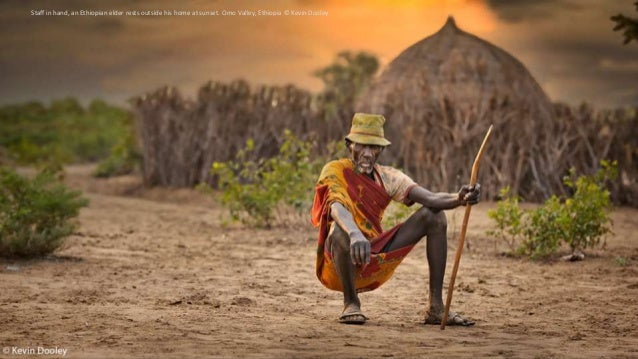 Staff in hand, an Ethiopian elder rests outside his home at sunset. Omo Valley, Ethiopia © Kevin Dooley