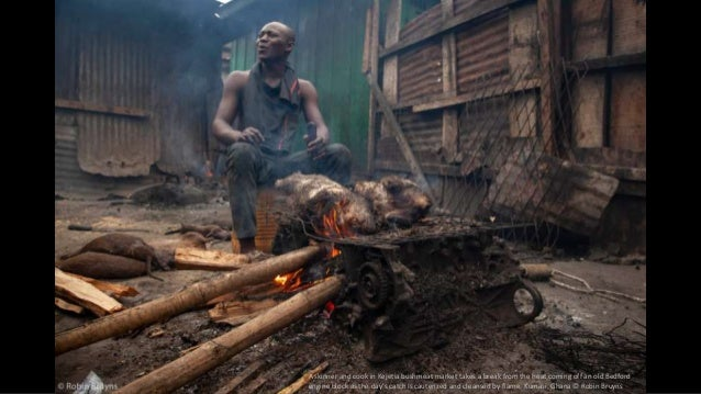 A skinner and cook in Kejetia bushmeat market takes a break from the heat coming off an old Bedford engine block as the da...