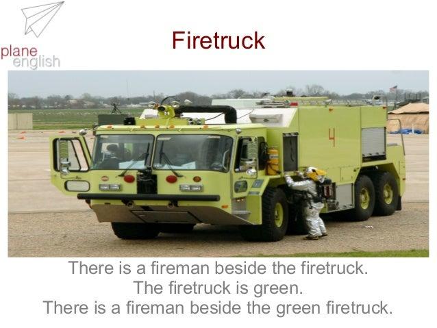 Firetruck  There is a fireman beside the firetruck. The firetruck is green. There is a fireman beside the green firetruck.