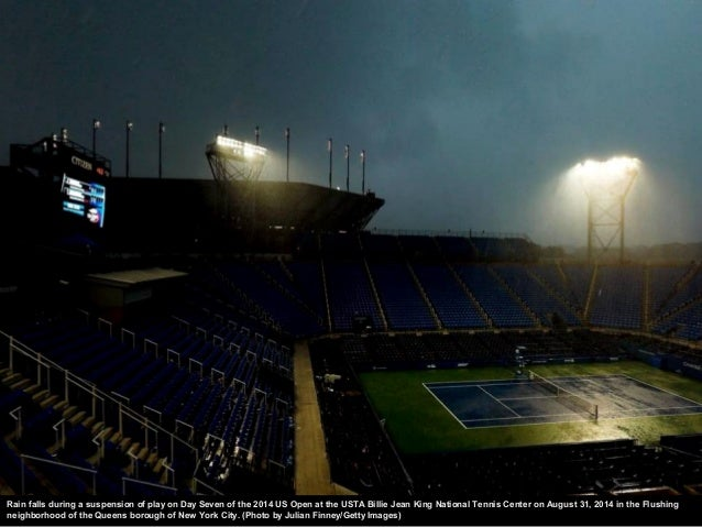 Fans shelter under umbrellas during a rain delay on Day Thirteen of the 2014 US Open at the USTA Billie Jean King National...