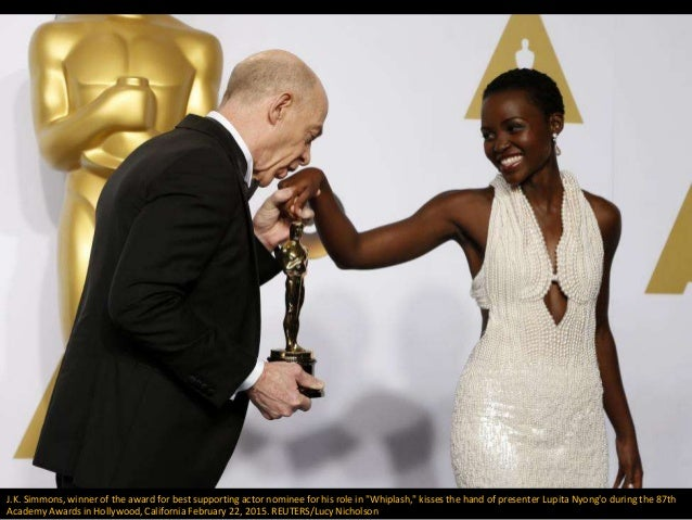 """J.K. Simmons, winner of the award for best supporting actor nominee for his role in """"Whiplash,"""" kisses the hand of present..."""