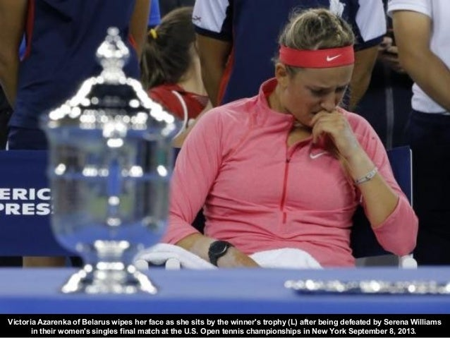 Victoria Azarenka of Belarus wipes her face as she sits by the winner's trophy (L) after being defeated by Serena Williams...