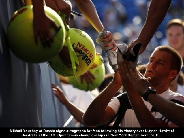 Mikhail Youzhny of Russia signs autographs for fans following his victory over Lleyton Hewitt of Australia at the U.S. Ope...