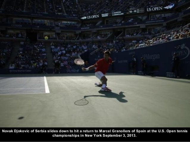 Novak Djokovic of Serbia slides down to hit a return to Marcel Granollers of Spain at the U.S. Open tennis championships i...