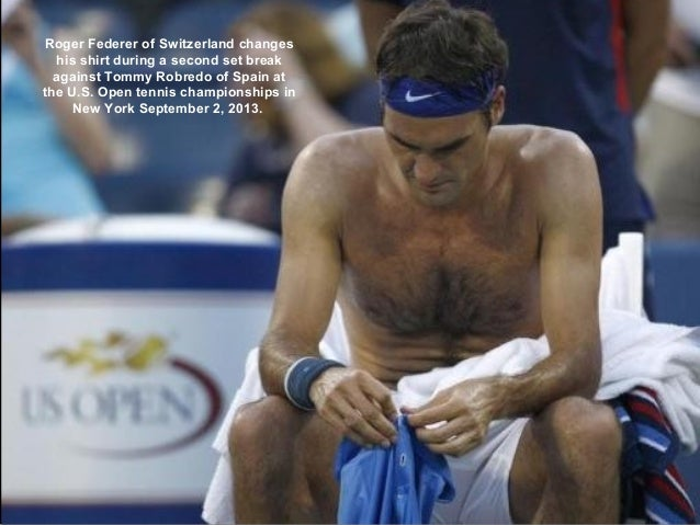 Roger Federer of Switzerland changes his shirt during a second set break against Tommy Robredo of Spain at the U.S. Open t...