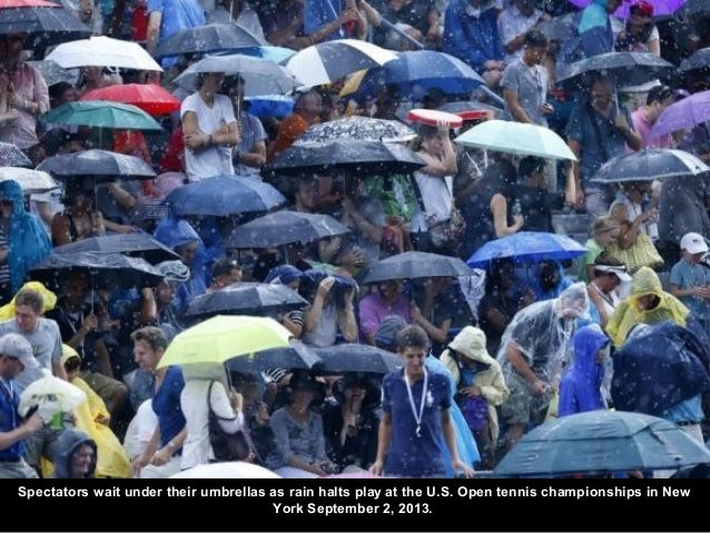 Spectators wait under their umbrellas as rain halts play at the U.S. Open tennis championships in New York September 2, 20...
