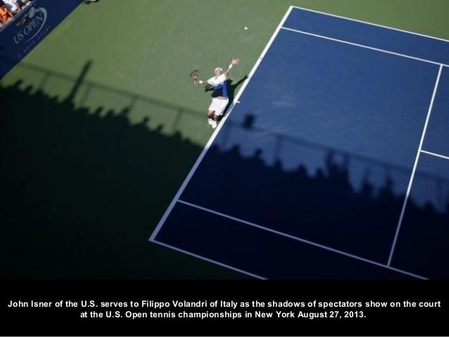 John Isner of the U.S. serves to Filippo Volandri of Italy as the shadows of spectators show on the court at the U.S. Open...