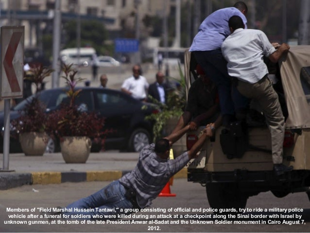 """Members of """"Field Marshal Hussein Tantawi,"""" a group consisting of official and police guards, try to ride a military polic..."""