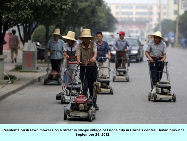 Residents push lawn mowers on a street in Nanjie village of Luohe city in Chinas central Henan province                   ...