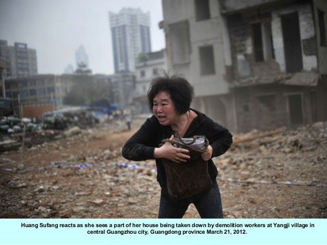 Huang Sufang reacts as she sees a part of her house being taken down by demolition workers at Yangji village in           ...