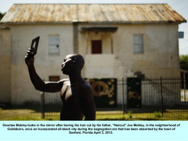 """Deontae Mobley looks in the mirror after having his hair cut by his father, """"Haircut"""" Joe Mobley, in the neighborhood of  ..."""