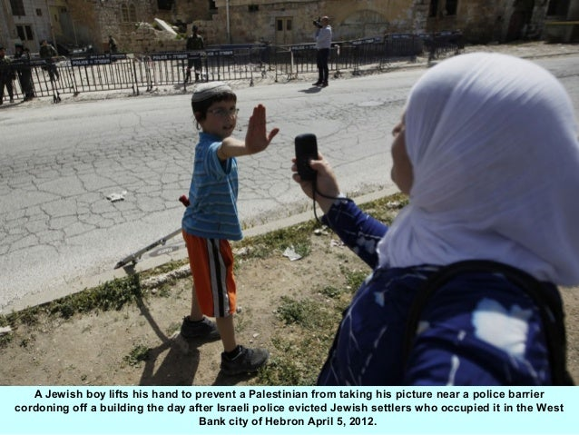 A Jewish boy lifts his hand to prevent a Palestinian from taking his picture near a police barriercordoning off a building...