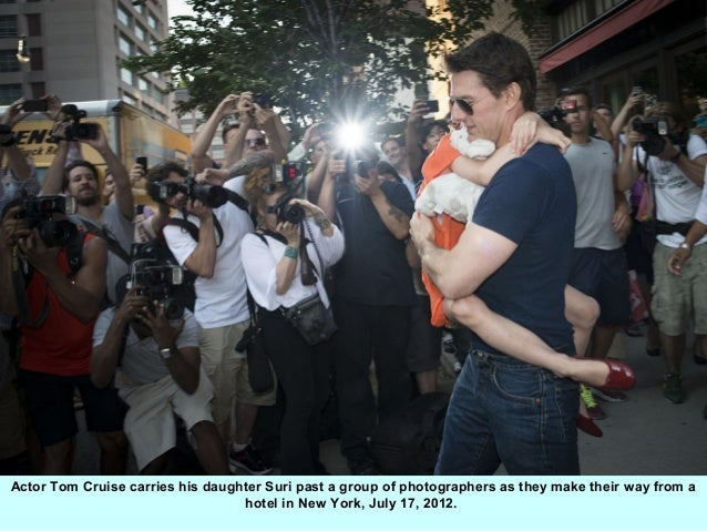 Actor Tom Cruise carries his daughter Suri past a group of photographers as they make their way from a                    ...