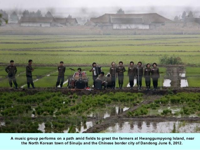 A music group performs on a path amid fields to greet the farmers at Hwanggumpyong Island, near    the North Korean town o...