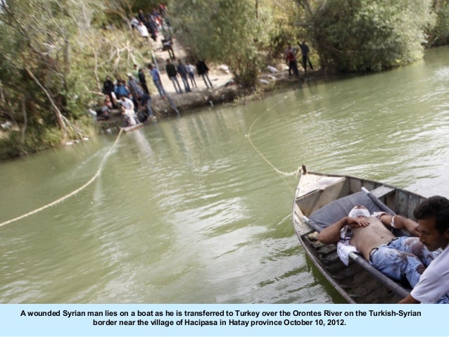 A wounded Syrian man lies on a boat as he is transferred to Turkey over the Orontes River on the Turkish-Syrian           ...