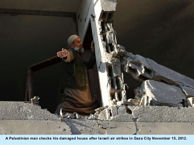 A Palestinian man checks his damaged house after Israeli air strikes in Gaza City November 15, 2012.