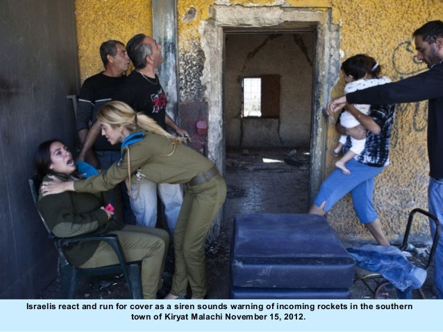 Israelis react and run for cover as a siren sounds warning of incoming rockets in the southern                           t...