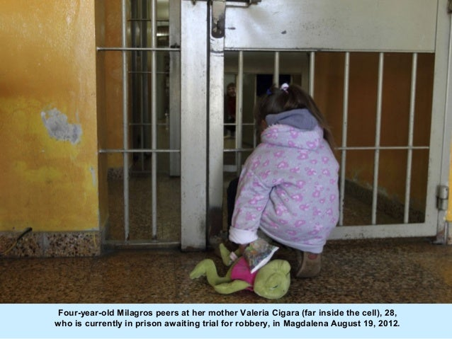 Four-year-old Milagros peers at her mother Valeria Cigara (far inside the cell), 28,who is currently in prison awaiting tr...