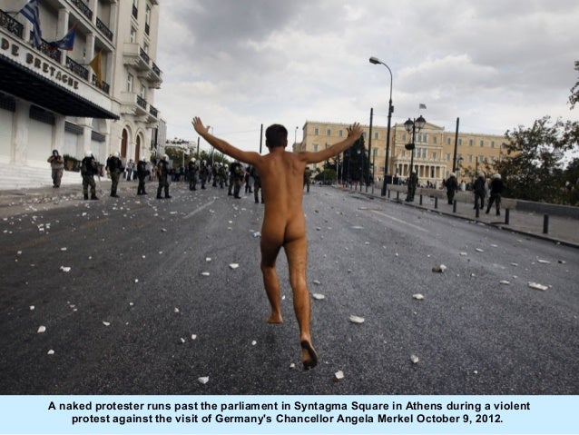 A naked protester runs past the parliament in Syntagma Square in Athens during a violent    protest against the visit of G...